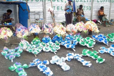 Vendors sell wreaths outside a funeral parlour.