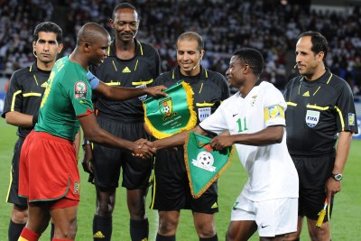 Samuel Eto'o of Cameroon and Chris Katongo of Zambia with Referee officals during the African Nations Cup match between Cameroon and Zambia .