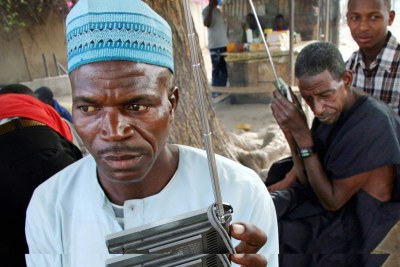Nigerians listen for the latest election news on their radios in Kano, northern Nigeria, 19 April 2007.