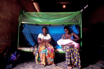 Two former abducted girls sit on a bed under the mosquito net.