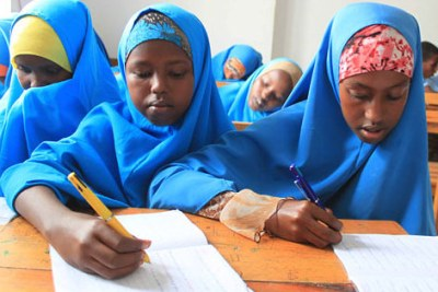 Students writing in class at Alnajah Primary School in Wardhigley district, Somalia.