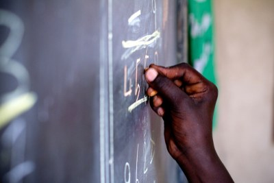 A student writes on a blackboard (file photo).
