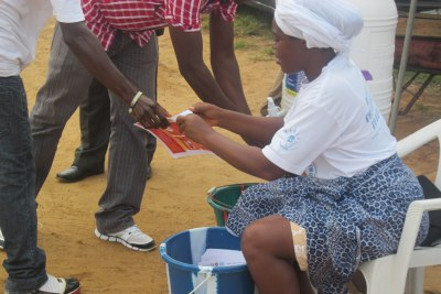 Women volunteers pray against Ebola while distributing fliers to passersby and asking them to wash their hands.