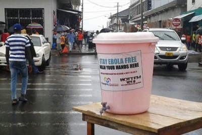 A large bucket of chlorinated water on the street of Central Monrovia for passersby to wash their hands.