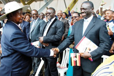 President Museveni (left) shakes hands with his political rival Kizza Besigye (file photo).