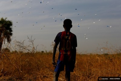 A boy watches sacks of food drop to the ground during a United Nations World Food Programme airdrop close to Rubkuai village in Unity State, northern South Sudan.