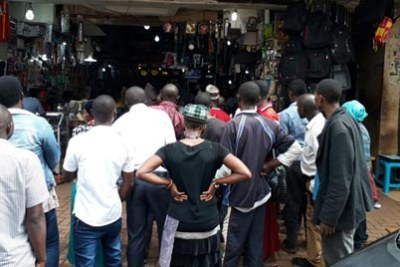 When news of Kaweesi's death spread, people gathered at one of the shops along Market Street in Kampala to watch television news updates.