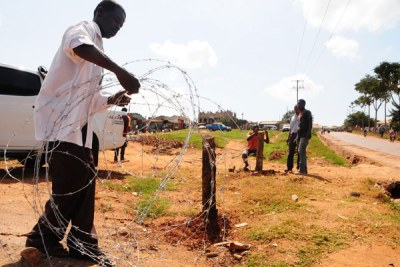 Ejection. Volunteers remove barbed wires which Mr Latimer Mpagi had erected around the contested land.