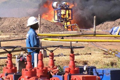 An expert watches a flaring experiment at one of the wells in the Albertine Graben (file photo).