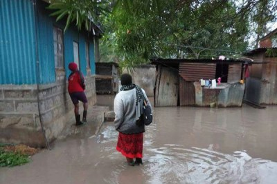 A woman and her son struggle to access their marooned home in Kilimambogo, Thika, Kiambu County on March 16, 2018.
