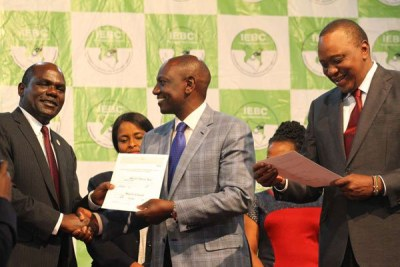 IEBC chairman Wafula Chebukati (left) presents Deputy President William Ruto with a certificate after Uhuru Kenyatta was declared winner of the presidential election, at the Bomas of Kenya on October 30, 2017.