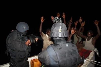 Portuguese marines apprehend several Somali pirates on a skiff.
