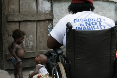 A young woman disabled by polio, her t-shirt reads: 'Disability is NOT inability'. Freetown, Sierra Leone.