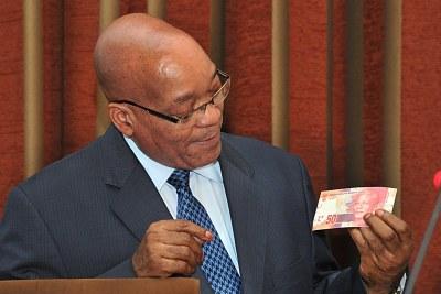 President Jacob Zuma holds the new currency bearing the image of former president Nelson Mandela.