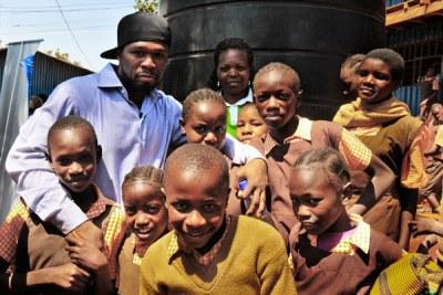 Rapper Curtis '50 Cent' Jackson with school kids in a Nairobi slum.