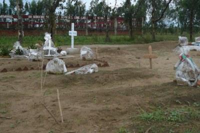 Tombes de victimes de l'attaque du 18 septembre 2011 à Gatumba au premier plan, et mémorial pour les victimes de l'attaque de 2004 à Gatumba