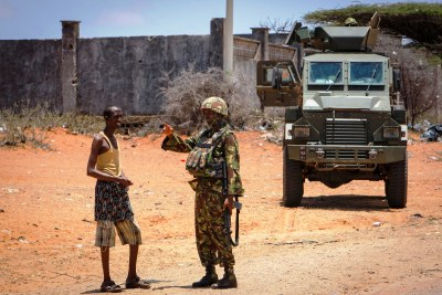 A Kenyan soldier serving with the African Union Mission in Somalia gestures during a conversation with a Somali man on at a roadside in the port city of Kismayo.