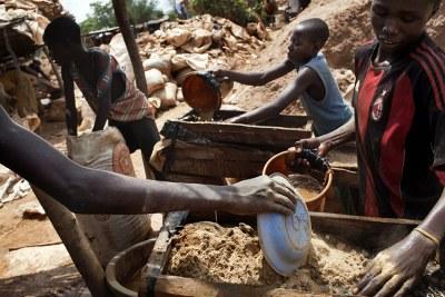 Les enfants travaillent dans le site de traitement à une mine d'or en Bagega