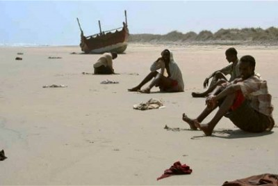 Ethiopian migrants wait for rescue on the beach.