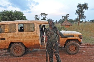 SPLM-N fighter standing in front of traditional tukul hut and mudded up rebel vehicle in Blue Nile state
