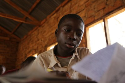 A 13-year-old boy, who mines gold, attends classes in a small-scale mining area in Mbeya Region, Tanzania. Work in mining impacts children's performance and attendance at school.