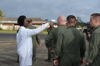 Marines from the Special Purpose Marine Air Ground Task Force Crises Response 14-2, out of Moron, Spain stand in line to have their temperature checked as they exit the KC-130 that brought them to Monrovia.