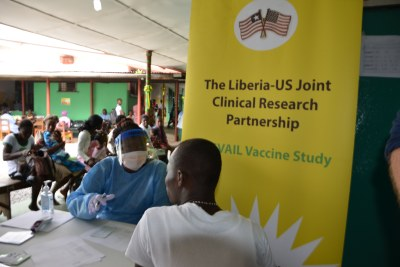 Liberian pharmacists, in protective gear, transfer the Ebola test vaccines from vials to syringes.