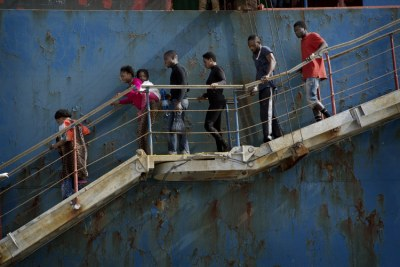Rescued migrants disembark from the cargo ship that rescued them (file photo).