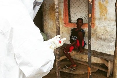 Health workers take blood sample from a young boy in the area where another 17-year-old died of Ebola.