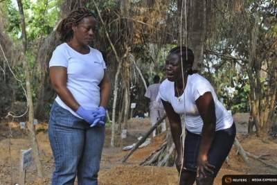 A health worker stands with a woman grieving over lost relative Tamai Kollie at an cemetery for victims of Ebola virus.