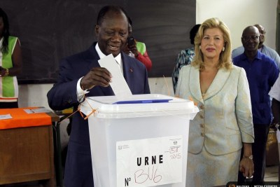 President Ouattara, accompanied by wife Dominique Folloroux-Ouattara, casts his vote. He is likely to win a second term.