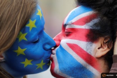 Two activists with the EU flag and Union Jack painted on their faces, kiss each other in front of the Bradenburg Gate to protest against Brexit in Berlin.