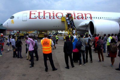 Passengers alight from an Ethiopian Airlines Airbus A350 at Entebbe International Airport.