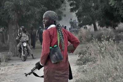 (Photo d'archives) - Un combattant de Boko Haram traverse la ville de Banki alors que des militants attaquent une caserne militaire à proximité.