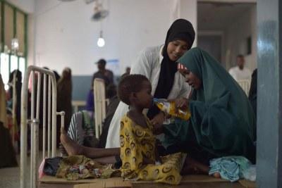 Une mère donne à sa fille un verre de sels réhydratants dans un hôpital de Mogadiscio, en Somalie.