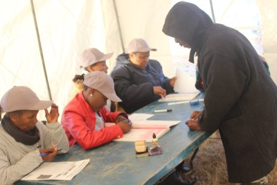 Officials assist a voter in Lesotho.