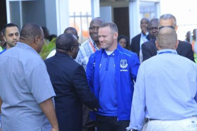 Everton's England striker Wayne Rooney, centre, greets officials upon arrival at the Mwalimu Julius Nyerere Airport in Dar es Salaam on July 12, 2017.