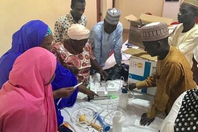 Hauwa Lassa, sage-femme, (troisième à gauche) fait une démonstration sur l'équipement d'accouchement fourni par UNFPA qui permettra des soins en toute sécurité.