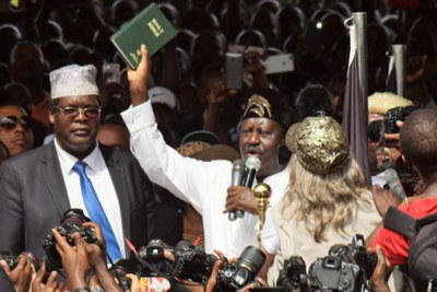 Holding up a green bible, Raila Odinga administered the oath himself - but without Kalonzo Musyoka, his running mate in the 2017 general election.