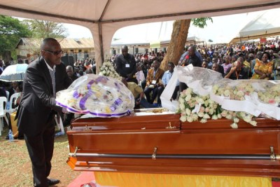 Security minister Henry Tumukunde lays a wreath on Susan Magara's casket. He represented President Yoweri Museveni.