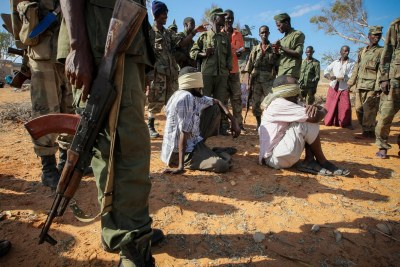 Alleged suspects of the extremist group Al-Shabaab are guarded by soldiers of the Somali National Army in Kismayo, Somalia in October 2012.