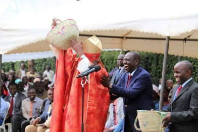 John Cardinal Njue (face partly hidden) lifts the cash donation given out by Deputy President William Ruto (second right) during a fundraiser in aid of St Thomas Moore, Kairuri Catholic Parish.