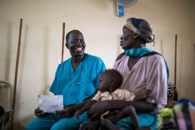 South Sudanese surgeon, Evan Atar Adaha, 52, and winner of the Nansen Refugee Award, sits with a refugee from Sudan and her malnourished son in the nutrition stabilization centre of Maban Hospital in the town of Bunj, Maban County, South Sudan on May 8, 2018.