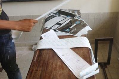 Un agent de la CENI présente la fiche des résultats du comptage numérique des bulletins d'un bureau de vote produit par la machine à voter le 31/12/2018 après le vote organisé le 30 décembre en RDC.