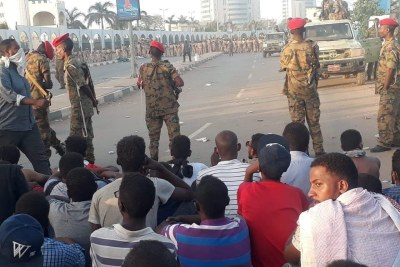 Soldiers stand in front of demonstrators in Khartoum on April 8, 2019.
