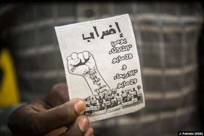 An employee of mobile phone company MTN holds a flyer supporting a general strike which he hands out to potential customers before turning them away, in Khartoum, Sudan, May 28, 2019.