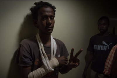 Wounded protester Mohmoud Abdulla flashes a peace sign while hiding in a corridor at Royal Care Hospital as Rapid Support Forces surrounded the building, in Khartoum, Sudan, June 4, 2019.