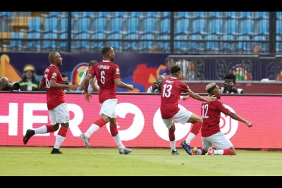Madagascar players celebrate after scoring a goal against Nigeria.