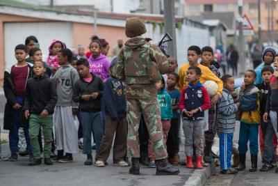 Children crowd around a SANDF member on patrol (file photo).