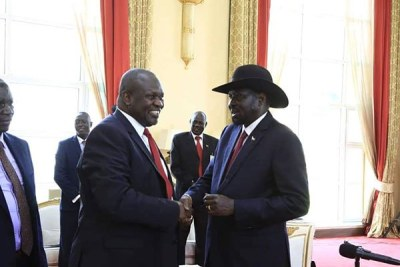South Sudan President Salva Kiir, right, shakes hands with opposition leader Riek Machar during a meeting at State House Entebbe, Uganda on November 7, 2019.